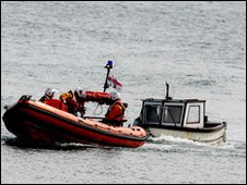 Fishing boat towed by lifeboat