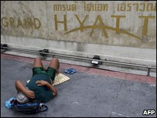 A protester sleeps in front of the Grand Hyatt hotel in Bangkok, 12/05