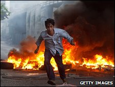 Protester runs from gunfire in Bangkok, Thailand (15 May 2010)