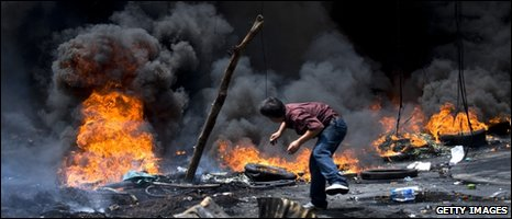 A protester throws wood on to a fire in Bangkok, 17/05