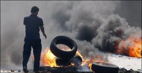 Protester throws fire on to burning barricade, Bangkok, 15/05/2010