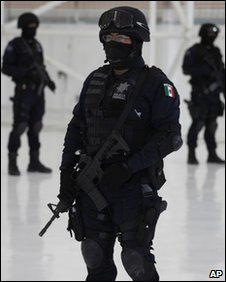 Mexican polcie stand guard as drug suspects are presented to the media - file photo April 2010