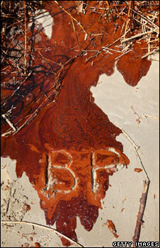 The letters BP drawn in oil-soaked sand
