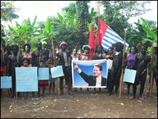 Tribespeople hold up a poster of David Cameron