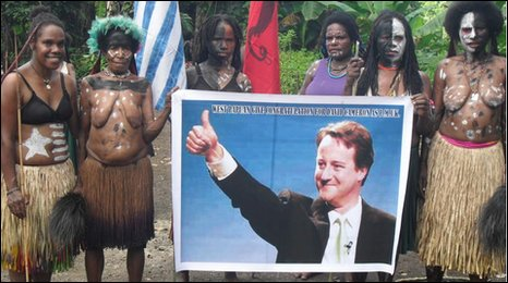 Tribespeople hold up a poster of David Cameron. Photo: Albert Tabuni