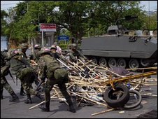 Soldiers clear away the bamboo barricades