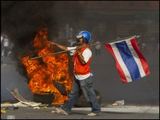 A red shirt anti-government protester holds a Thai flag as tyres burn