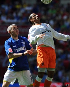 Kevin McNaughton challenges Blackpool's DJ Campbell