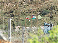 Lebanese, Palestinian and Hezbollah flags in Lebanon, seen from Israeli side of border