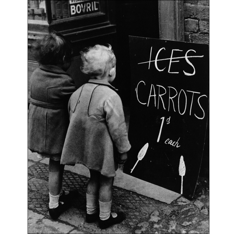 Two little girls read a board advertising carrots instead of ice lollies