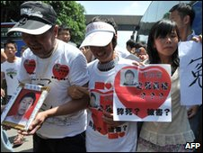 The parents and sister of a Foxconn employee who died hold tributes to him, outside the Foxconn plant in Shenzen, China
