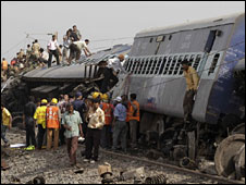 Rescuers stand close to the train's wreckage, 28 May