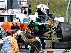 Adrian Sutil's car is lifted from the track