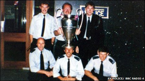 After a match in the police garage, the winning team pose with the cup