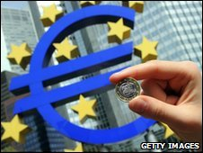 A women holds a euro coin outside the European Central Bank