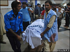 Rescue workers move the body of a victim who was killed when gunmen attacked Jinnah Hospital on 1 June 2010