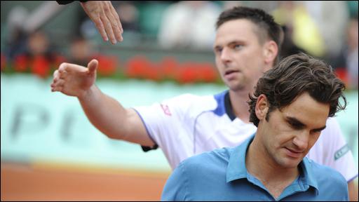 A dejected Roger Federer leaves the court followed by Robin Soderling