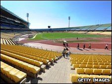 Stadium volunteers walk around the inside of the Royal Bafokeng Stadium on June 2, 2010 in Rustenburg.
