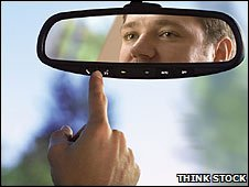 A man looking in a rear-view mirror