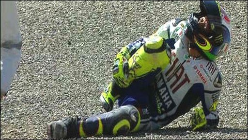 Valentino Rossi holds his injured leg
