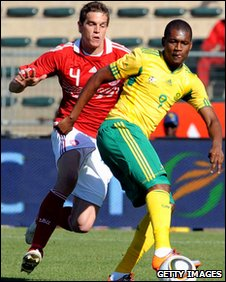 Katlego Mphela is challenged by Daniel Agger
