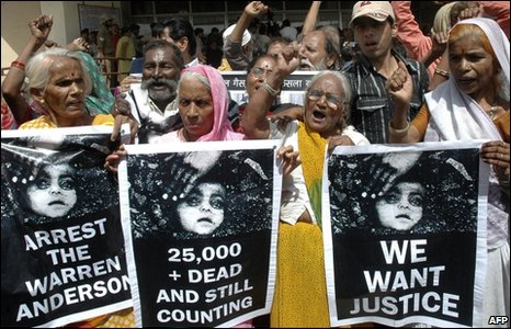 Demonstrators shout and wave placards outside a courthouse in Bhopal, India