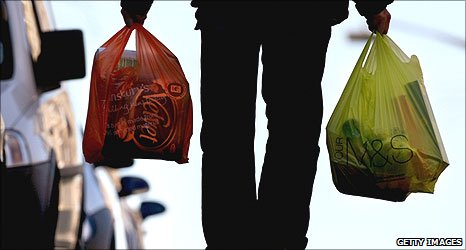 Person carrying shopping in plastic bags