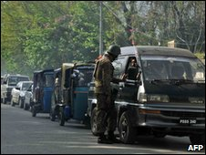 A Pakistani soldier questions commuters in a queue of vehicles, Mingora, 25 March 2010
