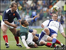 Bryan Habana passes the ball as referee Bryce Lawrence takes a tumble