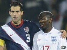 US defender Carlos Bocanegra hugs England midfielder Shaun Wright-Phillips