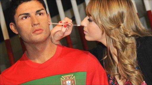 Woman touching up Tussaud's waxwork of Christiano Ronaldo