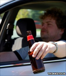 Motorist in left-hand drive car with beer