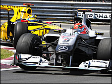 Michael Schumacher is chased by Robert Kubica's Renault