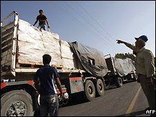 Palestinian workers inspect trucks carrying supplies arriving in Rafah