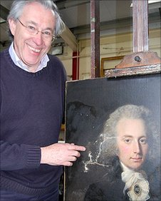 Mark Roberts and an oil painting under restoration