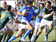 Italy's Andrea Masi makes a break as Springbok defenders close in