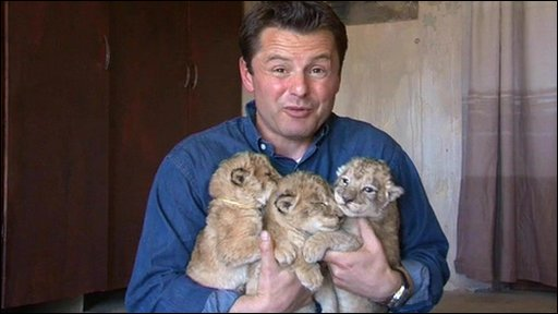 Chris Hollins clutches three lion cubs