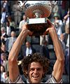Kuerten hoists the Muskateers cup after winning his third French Open final.