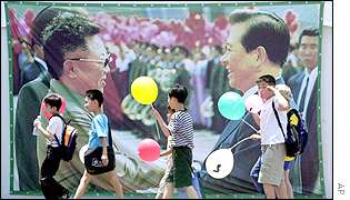 Children walk past a poster showing the historic meeting of South Korean President Kim Dae-jung and North Korean leader Kim Jong-il