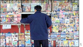 A Chinese man buys a magazine at a news stand on a Beijing street