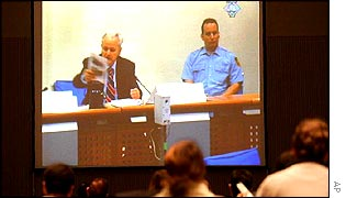 Slobodan Milosevic at his trial, watched by journalists