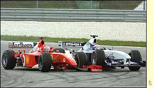 Juan Pablo Montoya (right) runs into Michael Schumacher at the first corner of the Malaysian Grand Prix