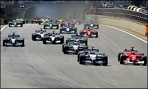 Michael Schumacher and Juan Pablo Montoya go into the first corner neck and neck