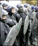 Riot police line up on the street