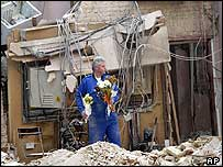 A rescue worker removes flowers from the wreck of the British Consulate