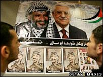 Palestinians look at posters of Yasser Arafat and Mahmoud Abbas