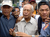 Retired Philippine Army General Fortunato Abat, centre, is escorted by plainclothes police officers after his arrest Thursday, Dec. 15, 2005 at the police headquarters in suburban Quezon City