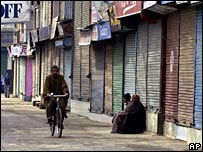 A man cycles past closed shops in Srinagar