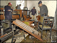 Pakistani policemen inspect the wreckage at the bomb blast site in Quetta
