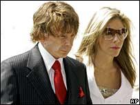 Фил Спектор входит в здание суда в дорогом костюме вместе со своей...